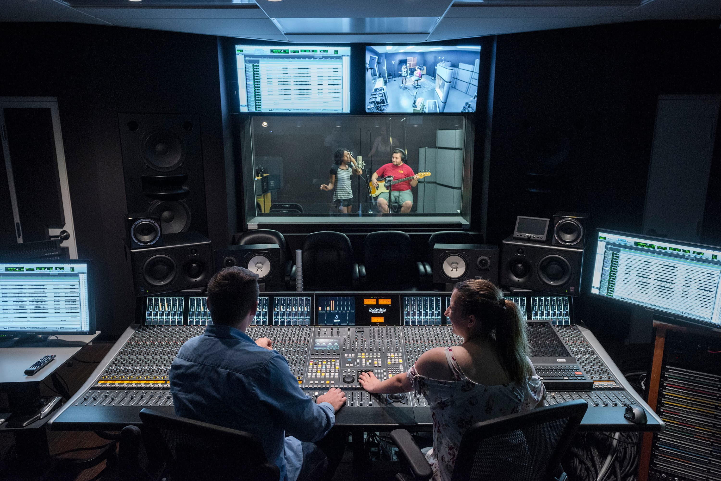 two technicians working a audio mixing board while two musicians perform in a recording booth