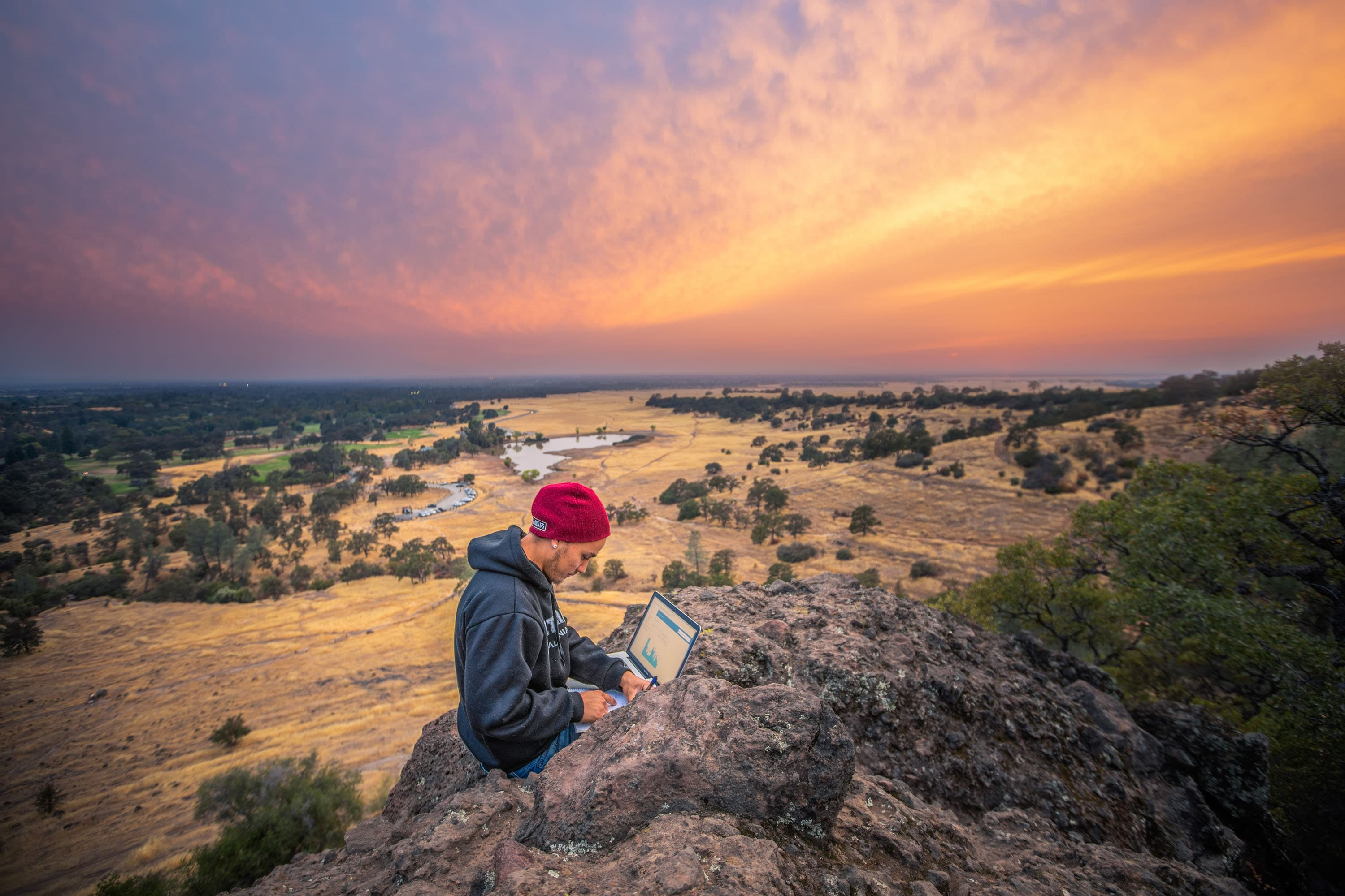 banner image- man on laptop ontop of a mountain overlooking openland and sunset