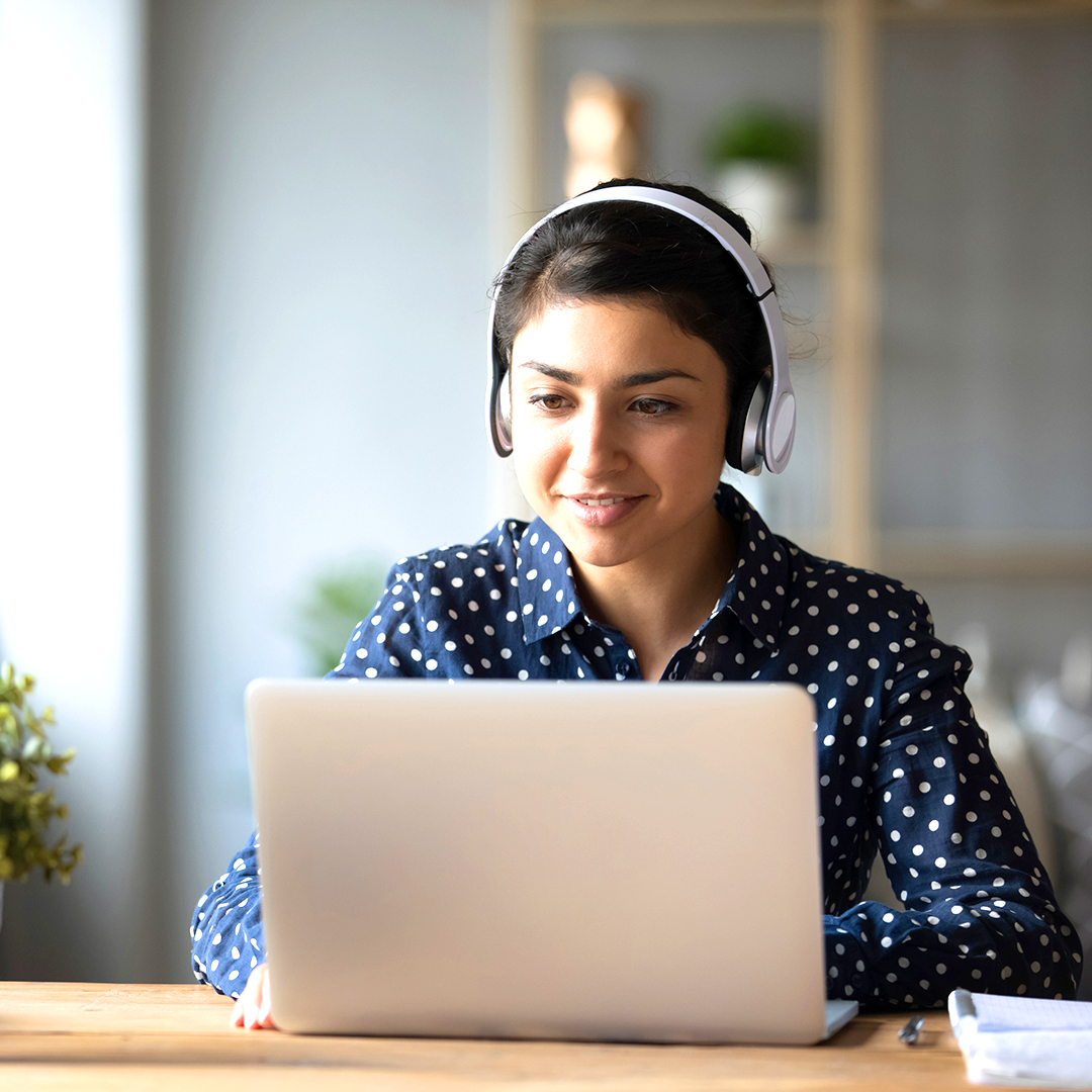A young woman wearing a headset looking at a laptop screen.