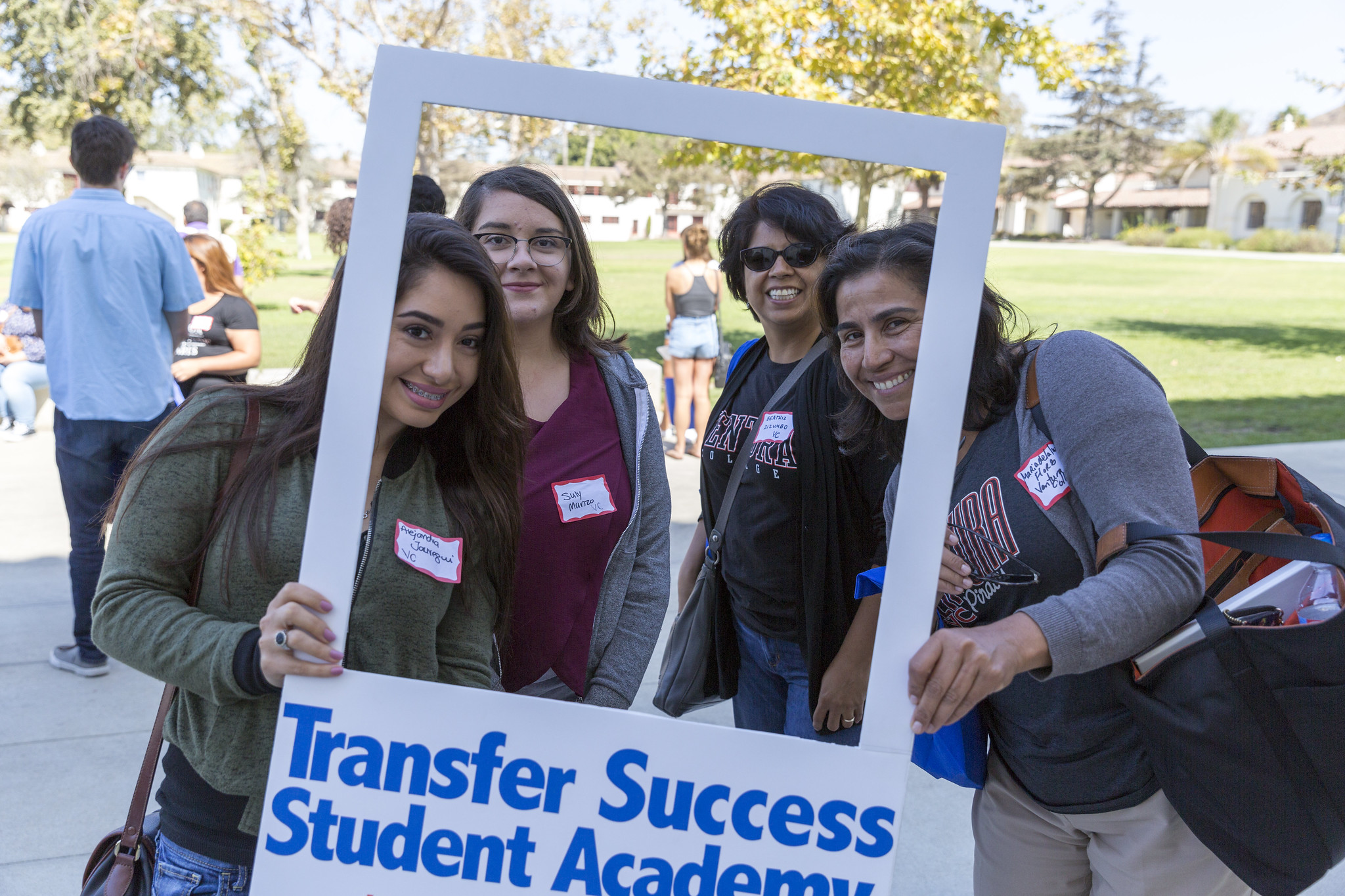 Two young women and their mothers hold a sign that reads Transfer Student Success Academy.