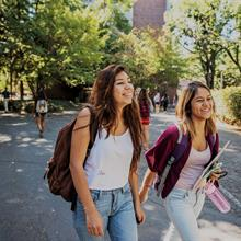 Smiling students walk across campus on a sunny day.