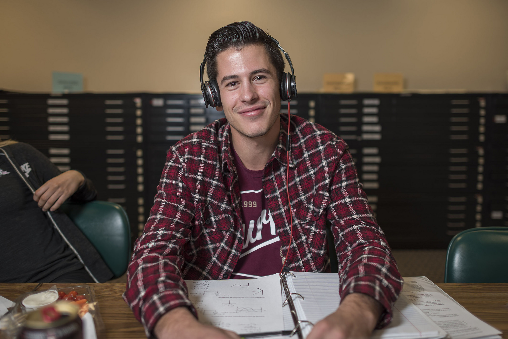 Male student with headphones on studying in the  library.