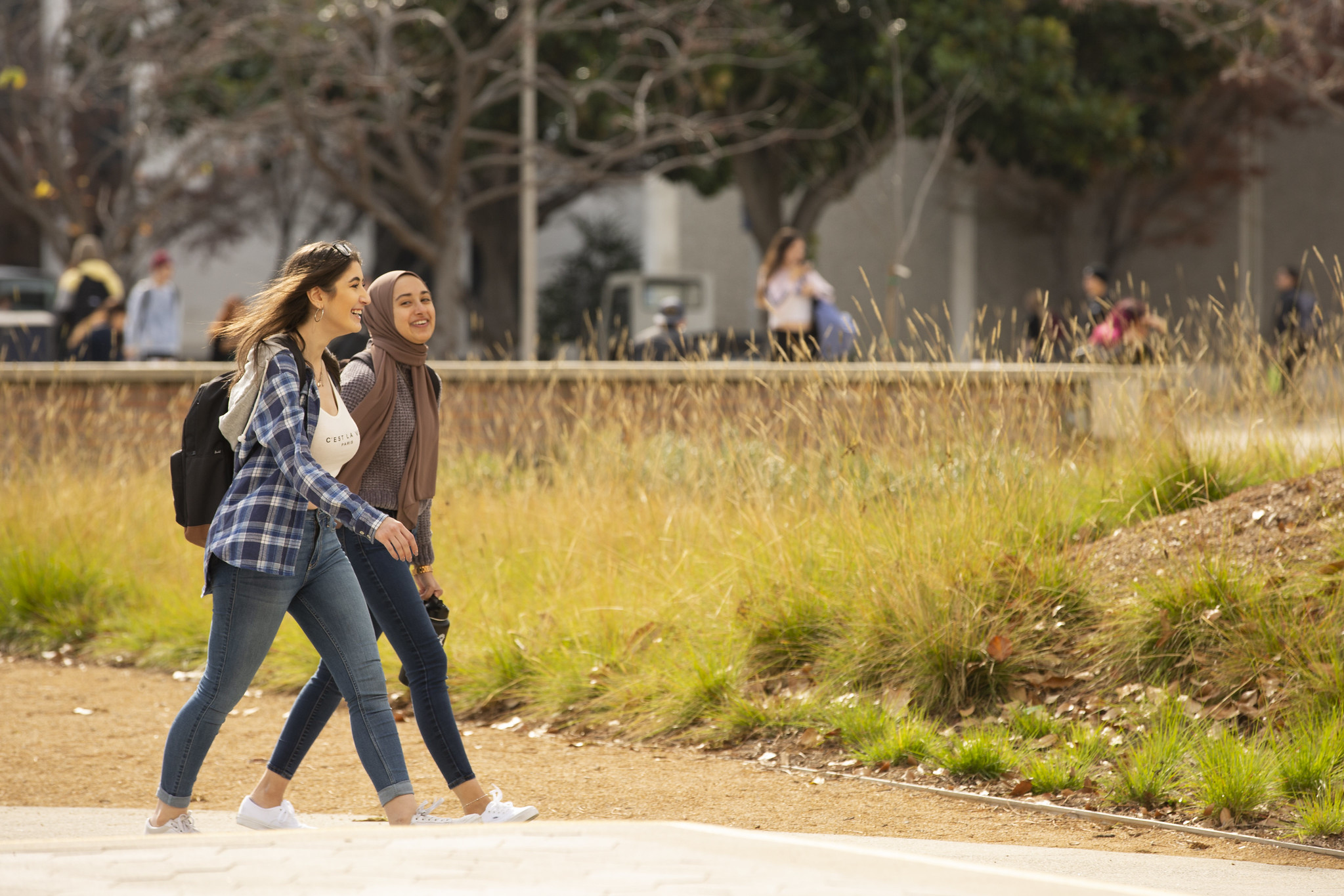 Two young women walking across a college campus talking with one another.