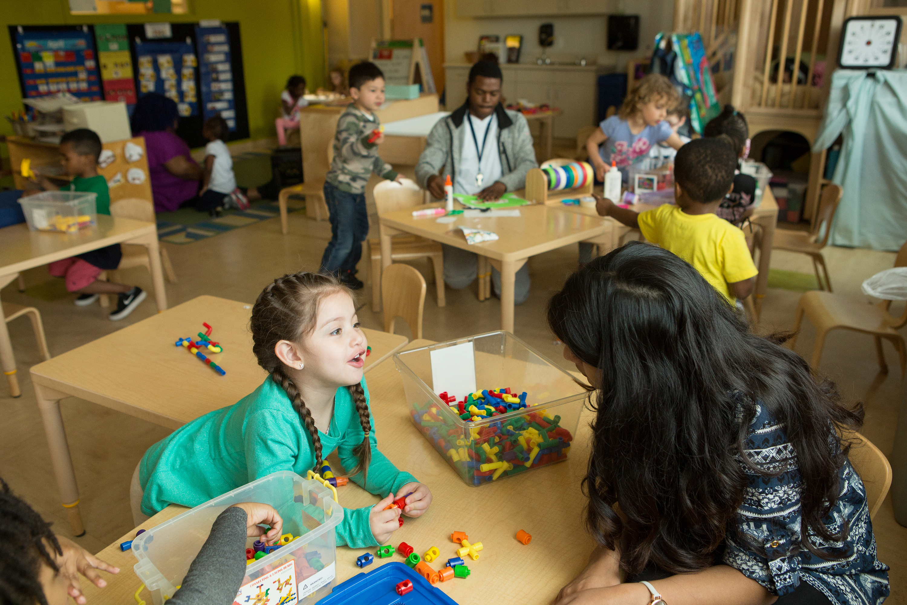 Young children and teachers play with building sets in a classroom.