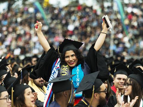 Female graduate raises both arms in triumph at Cal State Monterey Bay