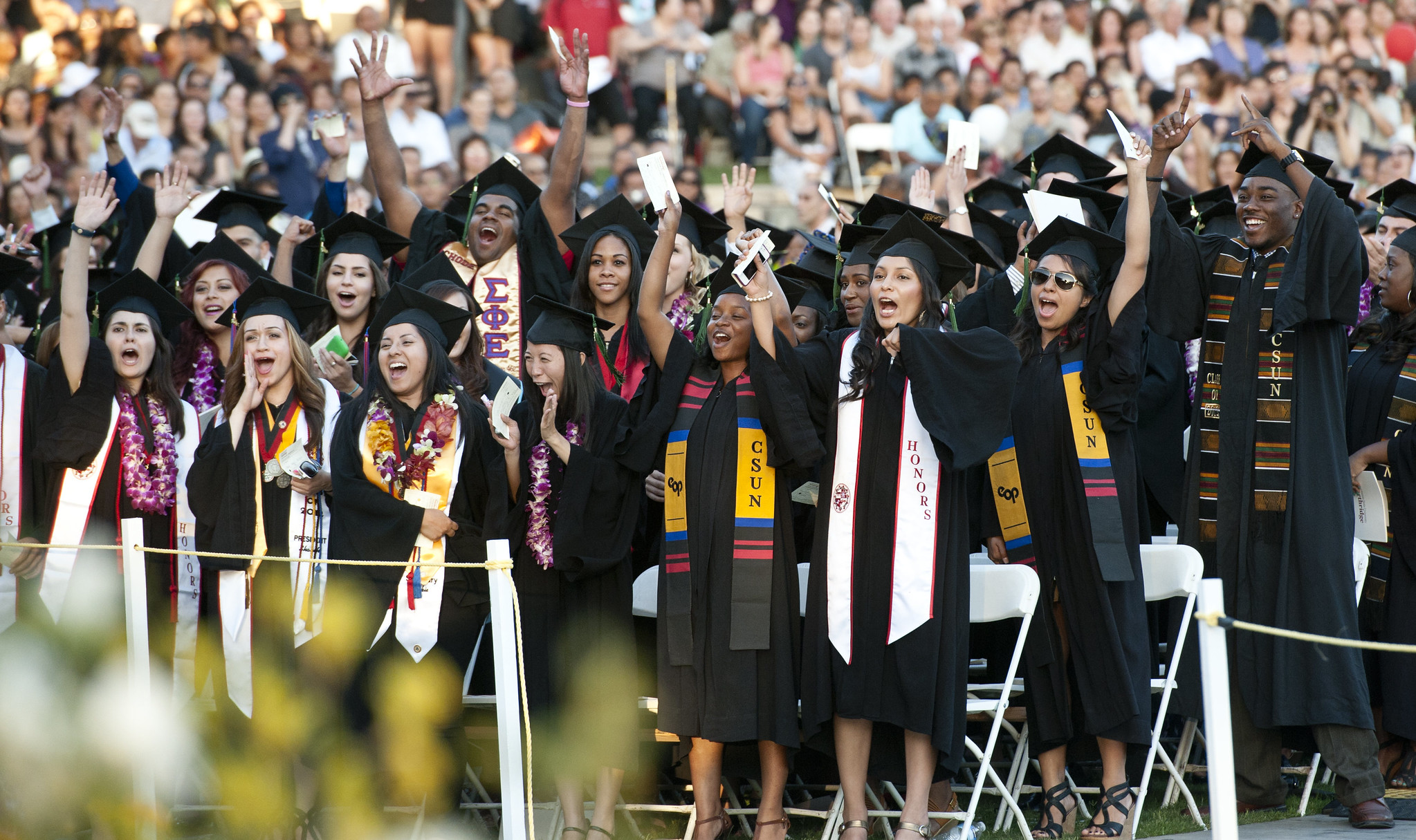 A large group of people wearing graduation caps and gowns cheering and smiling.