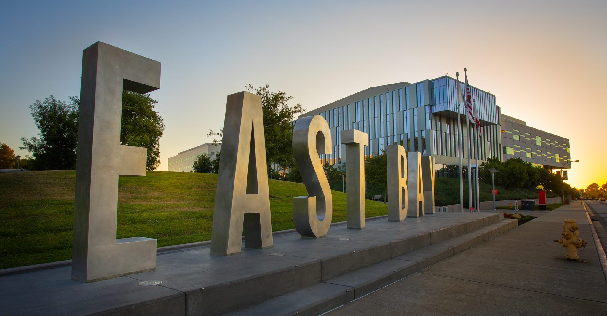 A close up of giant letter that spell East Bay on the campus.