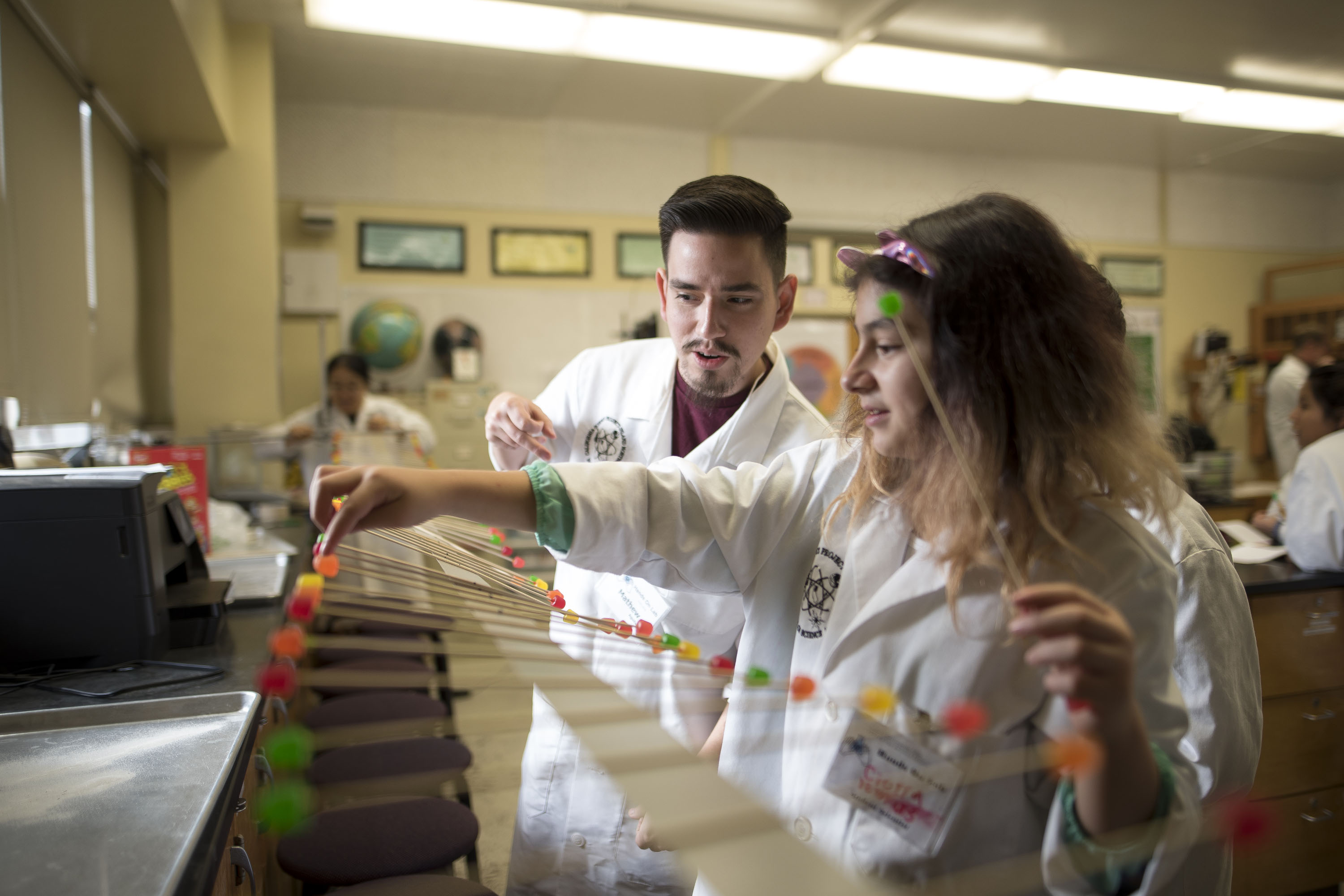 Male Chico State student working ona  science activity with a middle or high school female student.