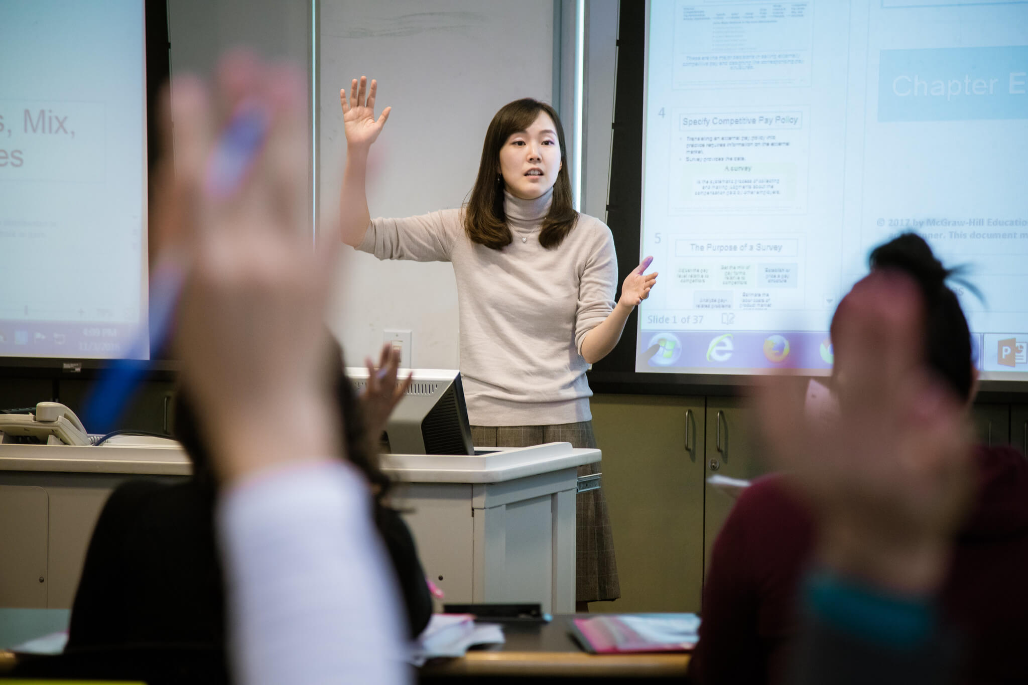 Female teacher lecturing a class in front of a projector screen