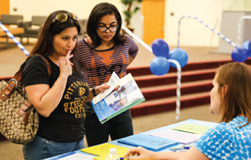 photo of student and parent getting materials at campus