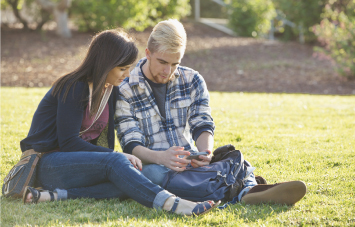 couple looking at phone while sitting on campus grass