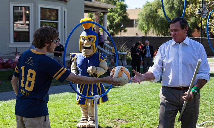 Chancellor White hands a ball to a quidditch from San José State