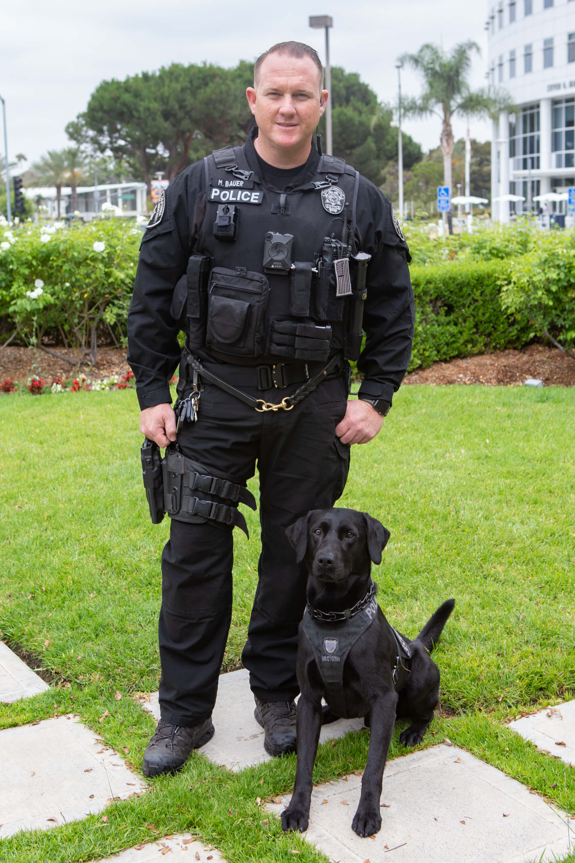 Officer Bauer and his black Lab Glock, both in uniform.
