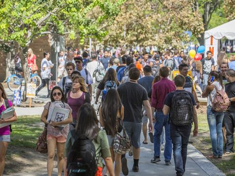 crowd of students walking on campus