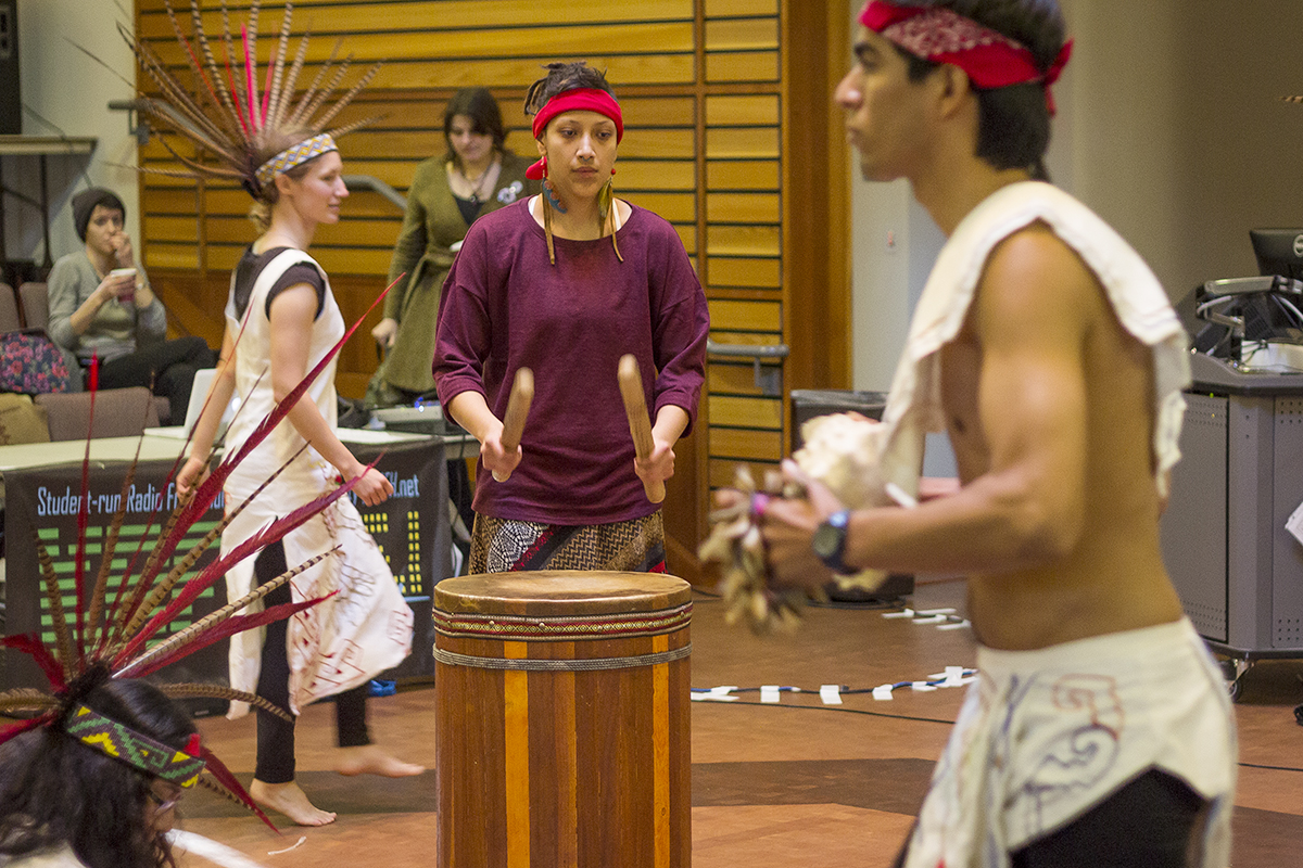 Students performing and beating a drum