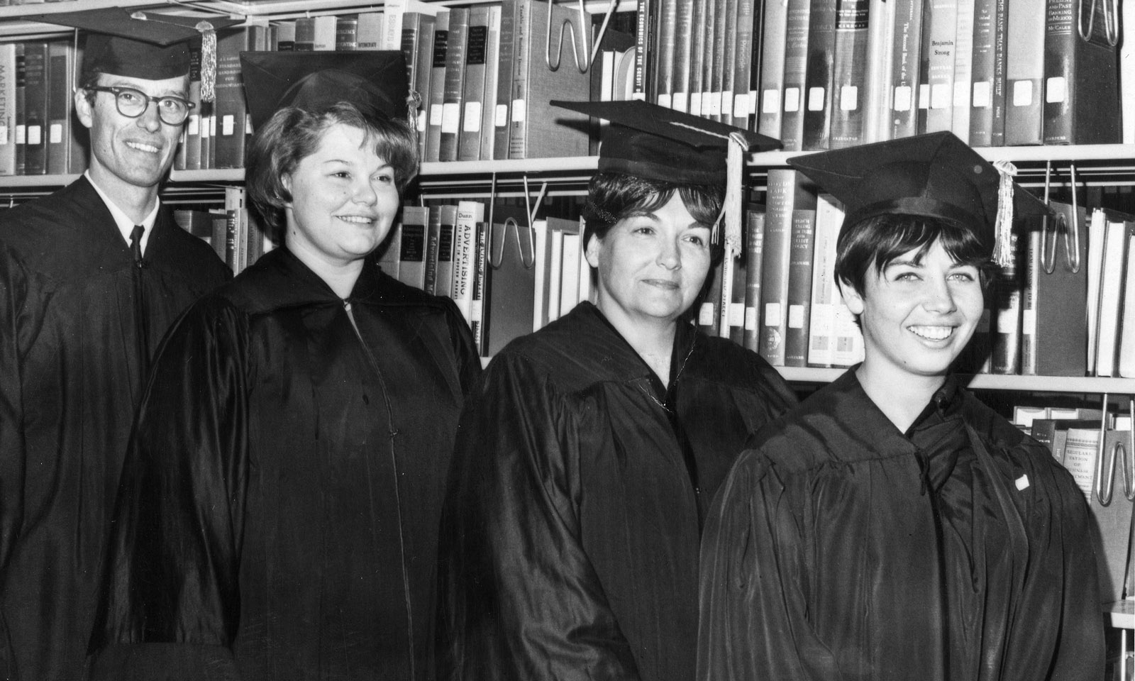 The first four graduates of CSUDH stand in the campus library, June 9, 1967. (left to right) William Hart, Pamela Striplin, Othi