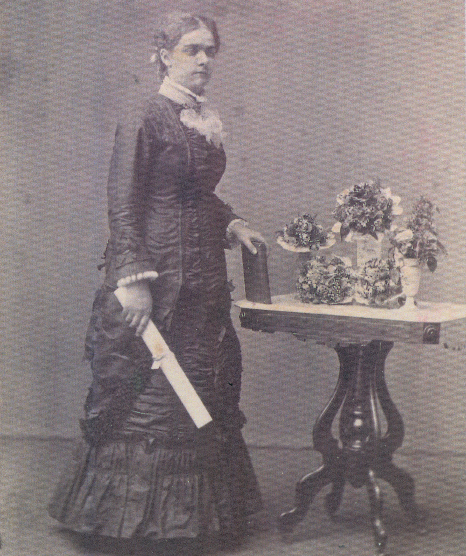 Sarah Locke poses in her graduation photograph, May 21, 1880. The dress worn in the photograph is also in the Sarah Locke Smith
