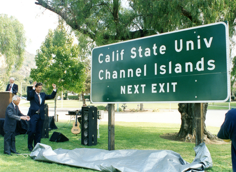 CHANNEL ISLANDS   1999 California State Assembly members Nao Takasugi (left) and Jack O'Connell (right) reveal the official campus road sign to be placed along the 101 Freeway in Camarillo during the planning stages of the university. The campus officially opens three years later.