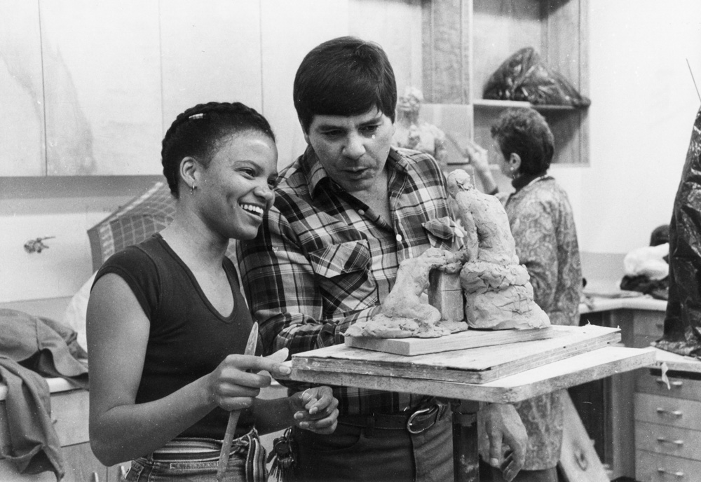 1983 Professor John Goders (right) examines an art table containing a clay sculpture in progress by an art student.