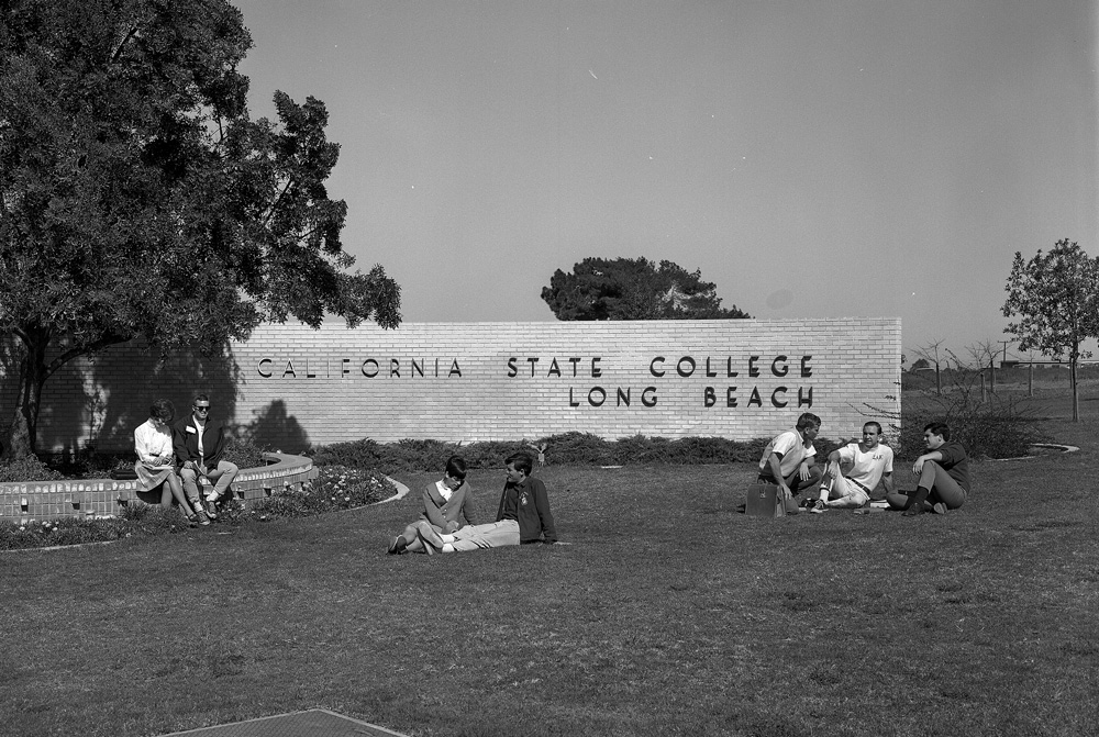 1962Students lounge on the lawn in front of CSULB's sign.