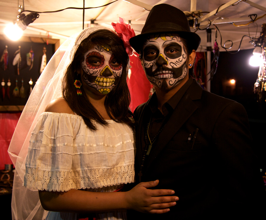 A couple dresses in traditional Dia de los Muertos attire.