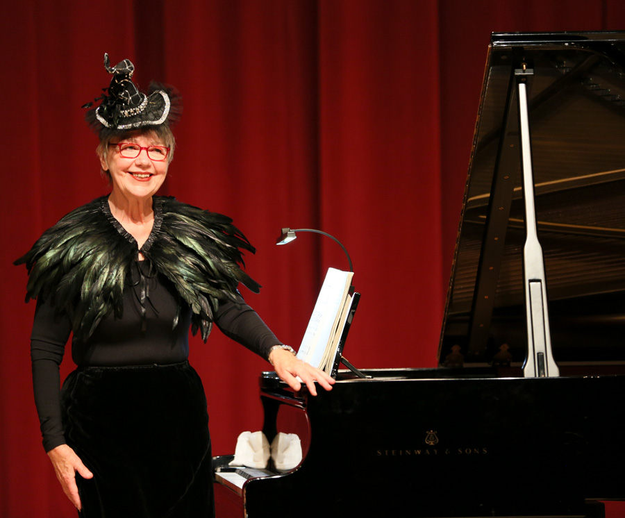 Music professor Victoria Neve stands at a piano.