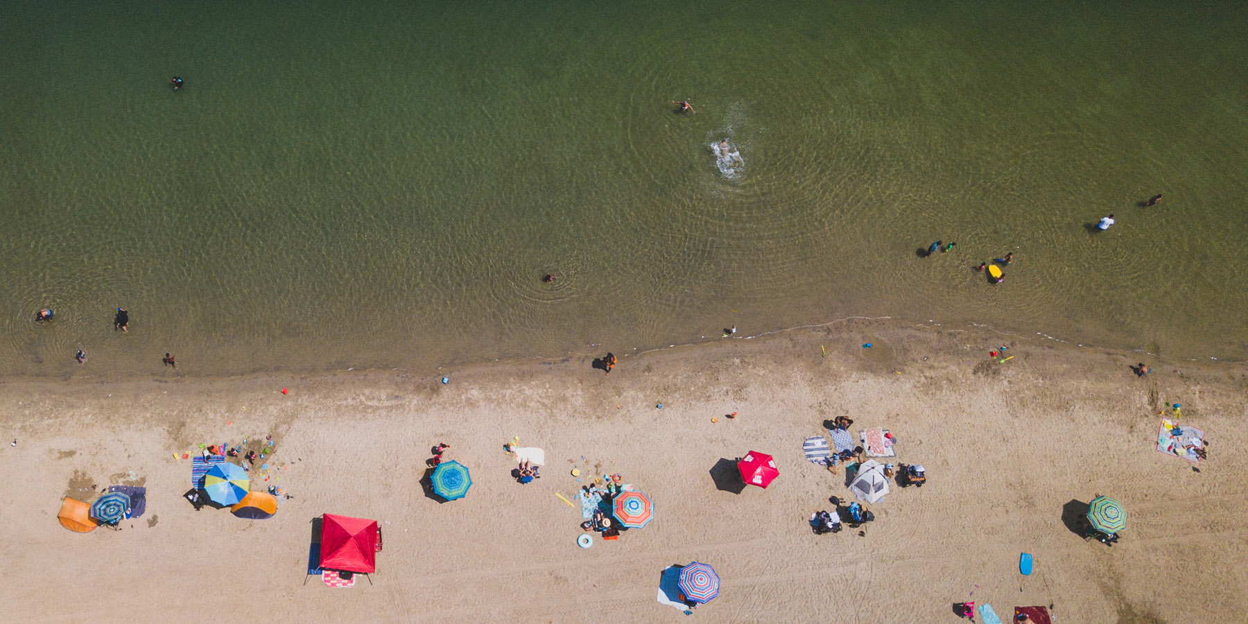 Beachgoers sit under umbrellas by the water.