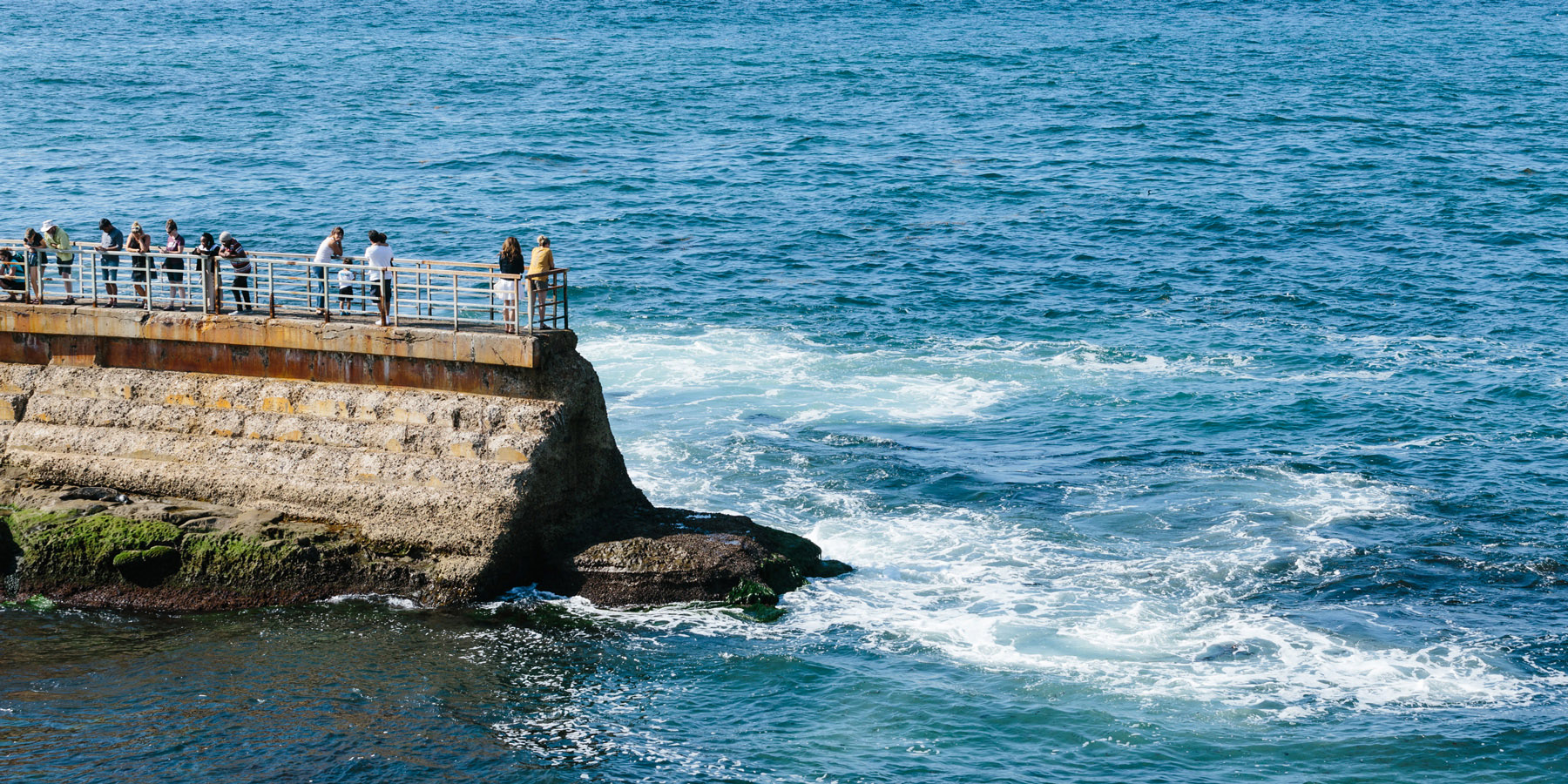 People stand on a seawall that juts into the ocean.