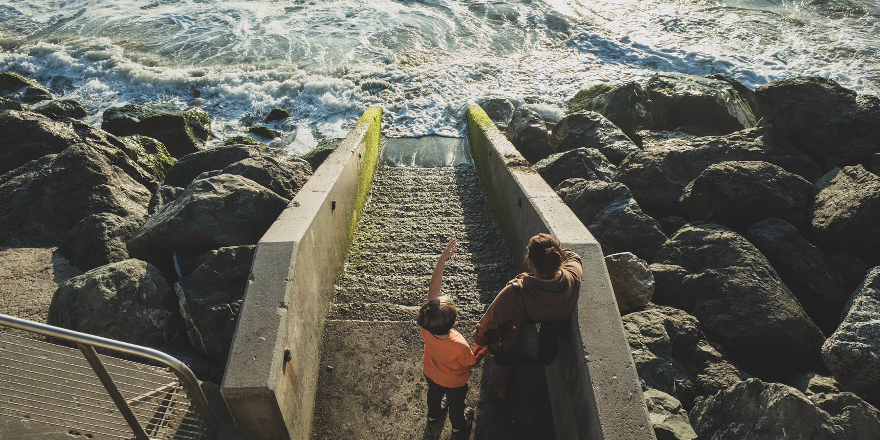Two people stand on stairs that descend into the ocean.