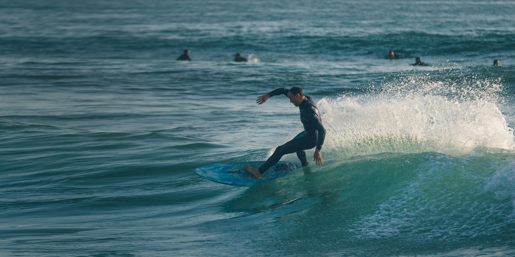 A surfer catches a wave.