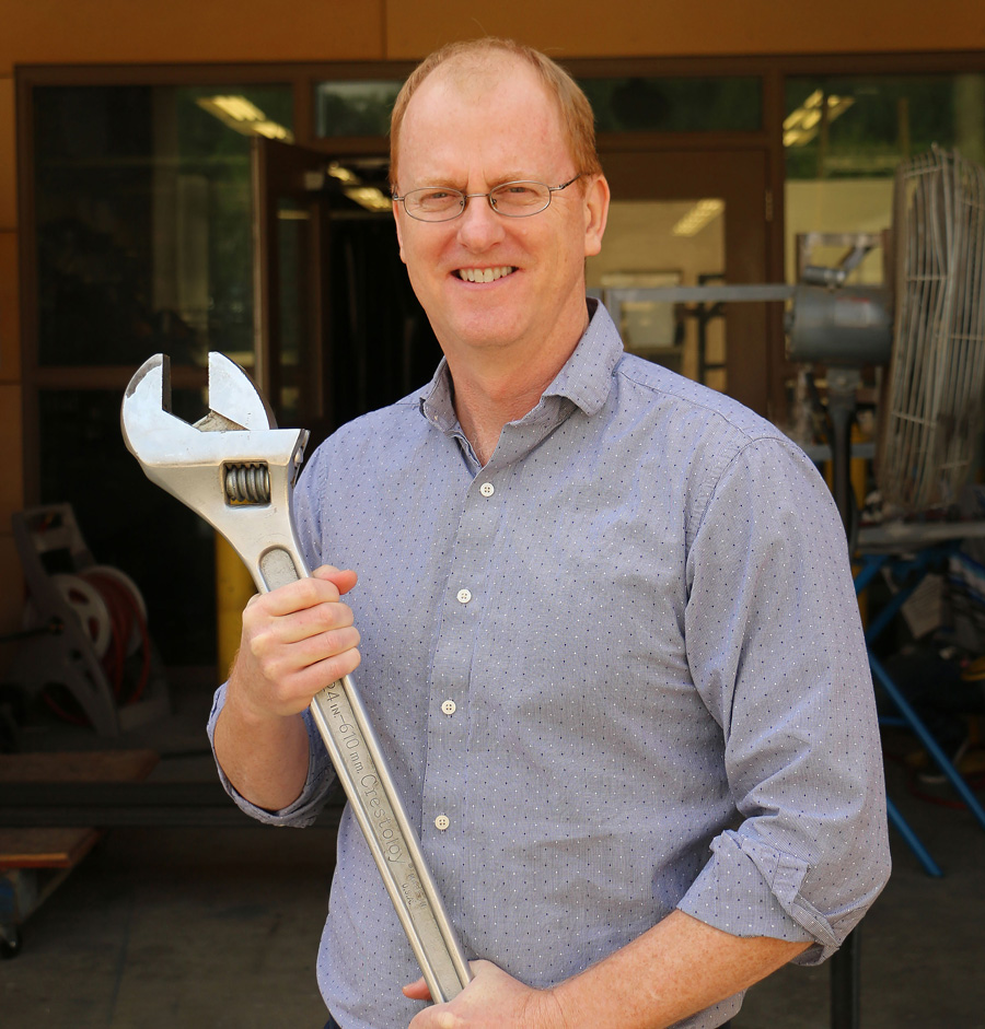 Dr. Brian Self holds an oversized wrench.