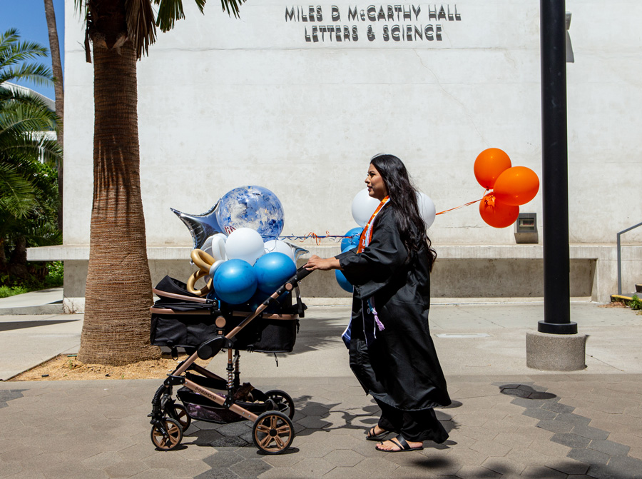 woman pushing stroller filled with ballons on a college campus