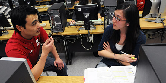CSU Fullerton student Anthony Kress works with client Madoka Kitahara on preparing a tax return