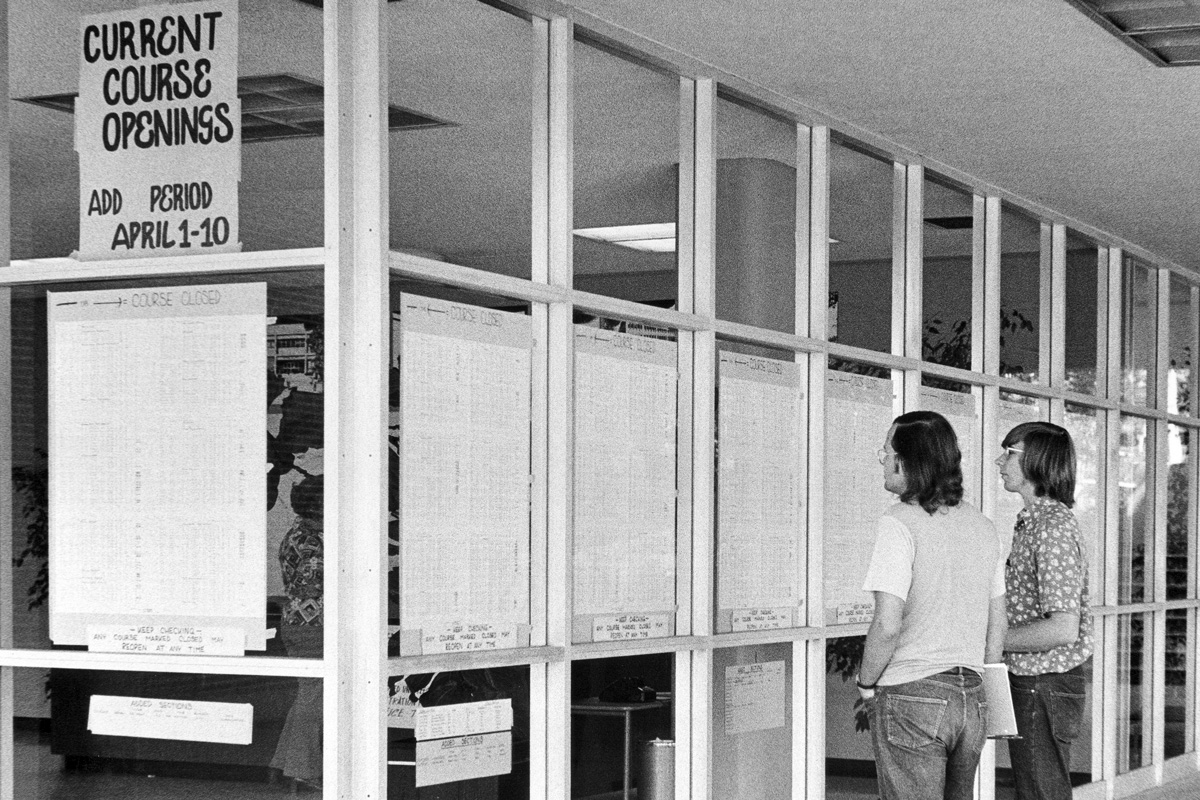 Students looking at a list of add/drop classes in a window of the Administration Building at Cal Poly Pomona in spring of 1974.