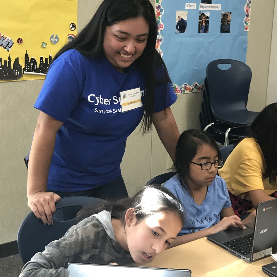 San José State Civic Action Fellowship Program Coordinator Joanna Solis working with two girls through the Cyber Spartans progra