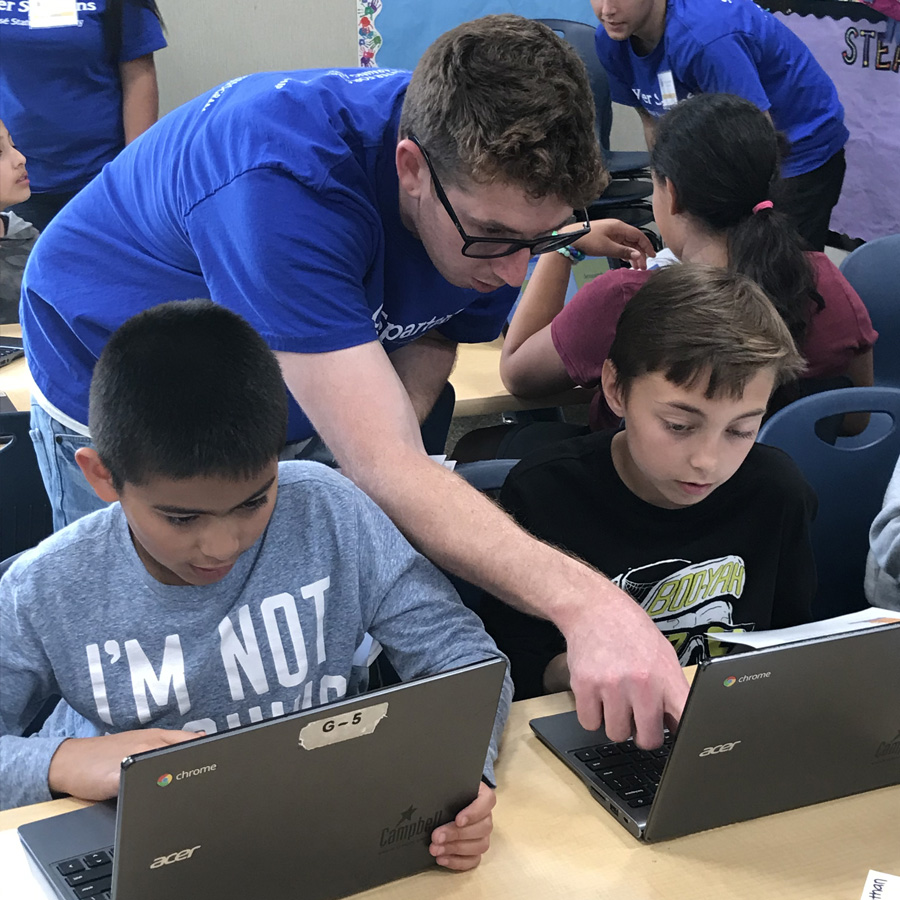 SJSU student Christopher Conetta helping two boys on laptops through the Cyber Spartans program.