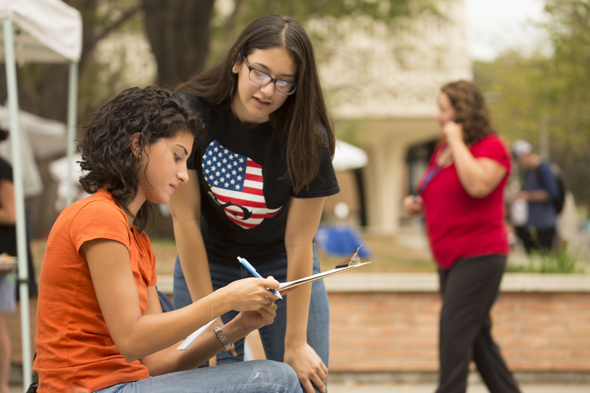 CSUF Lobby Corps member Amanda Martinez, right, helps Nageen Jalali (English/philosophy major) register to vote on September 20,