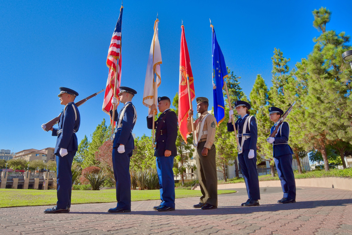 Members of the military stand at attention during an annual Wreath Laying Ceremony at the San Diego State War Memorial. Photo pr
