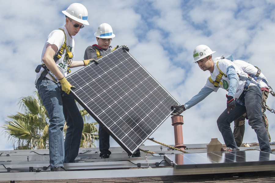 Cal Poly Pomona electrical engineering majors Johnny Bautista (center) and Sean McClanahan (left) assist Grid Alternative worker Miguel Rodarte, March 20, 2018. The students volunteered to set up solar panels for low-income families during spring break.
