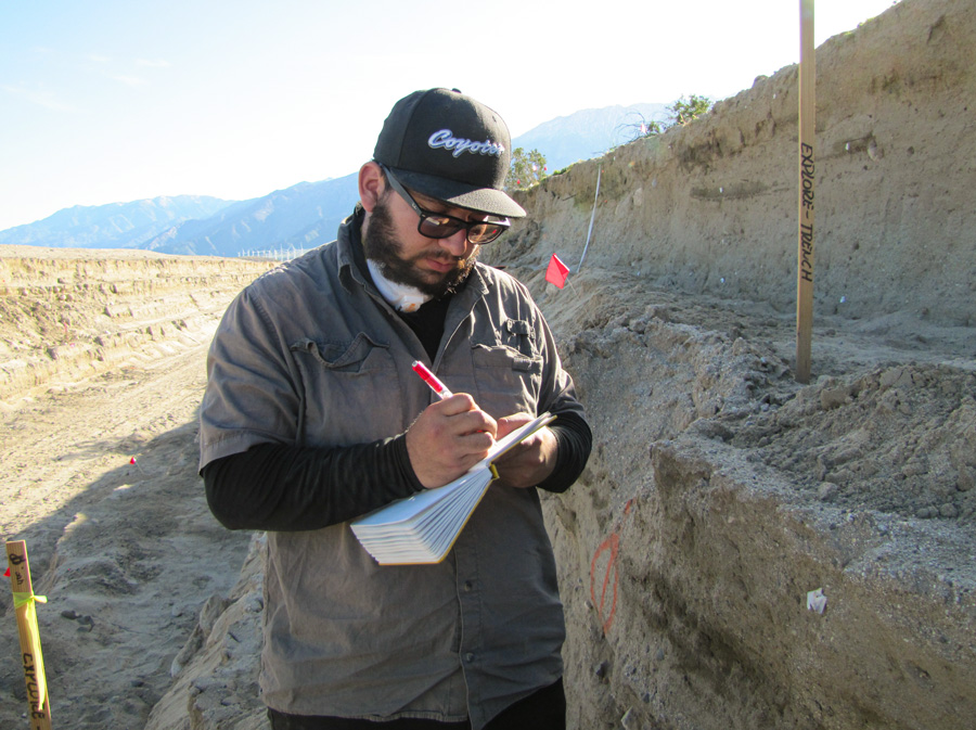 Under the direction of Dr. McGill, Bryan Castillo studies sediment layers of a 40-meter section of a trench dug along the San Andreas Fault.