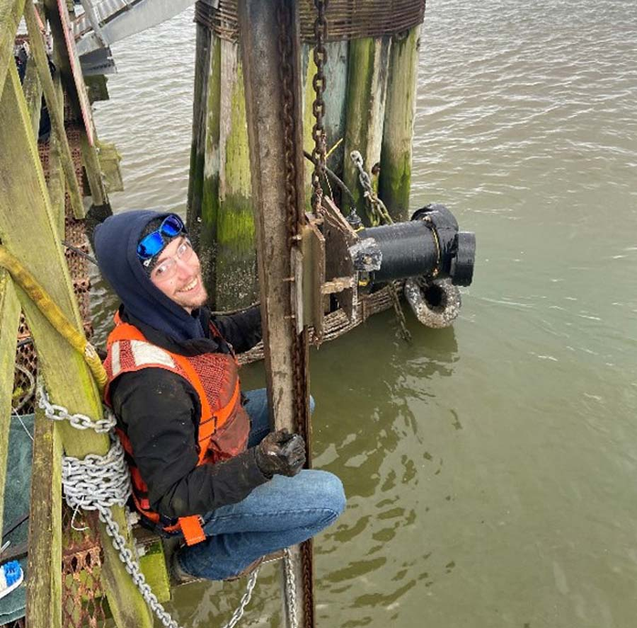 Bennett Hosselkus, oceanography/physics undergraduate student and PORTS technician, inspects a newly installed ADCP.
