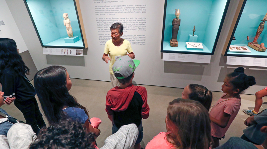 A Robert and Frances Fullerton Museum of Art docent gives local students a tour of the Egyptian collection.