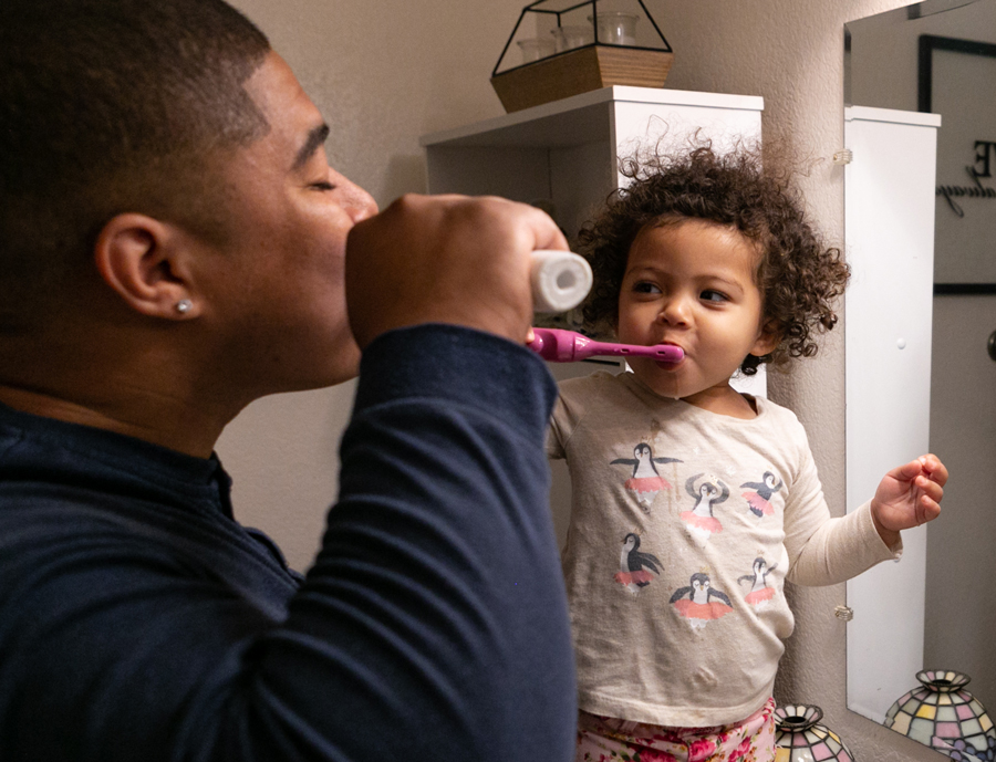 Steven and his daughter brushing their teeth.