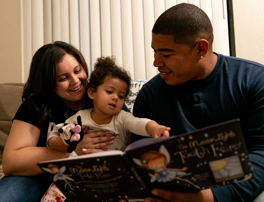 Steven reading a children's book with his wife and daughter.
