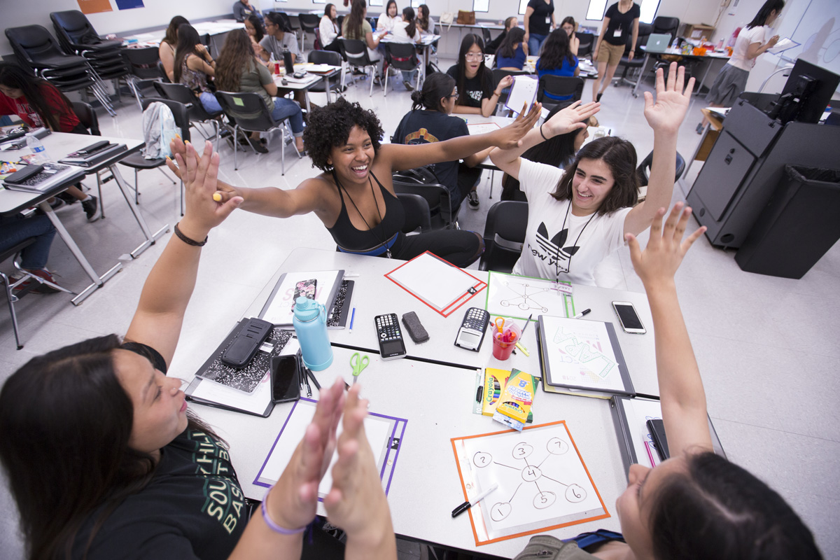 Brynn Campos, middle left, celebrates with her teammates after correctly solving a polynomial equation at CSUF
