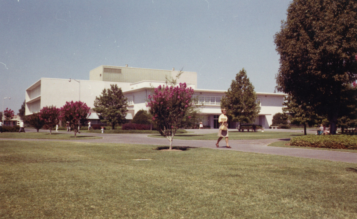 A student strolls by the Old Library building (currently Lassen Hall) on her way to class, 1964.