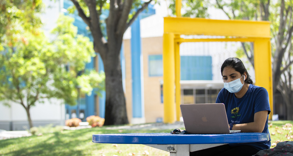 female student wearing a facemask while sitting at an outdoor table using a laptop computer