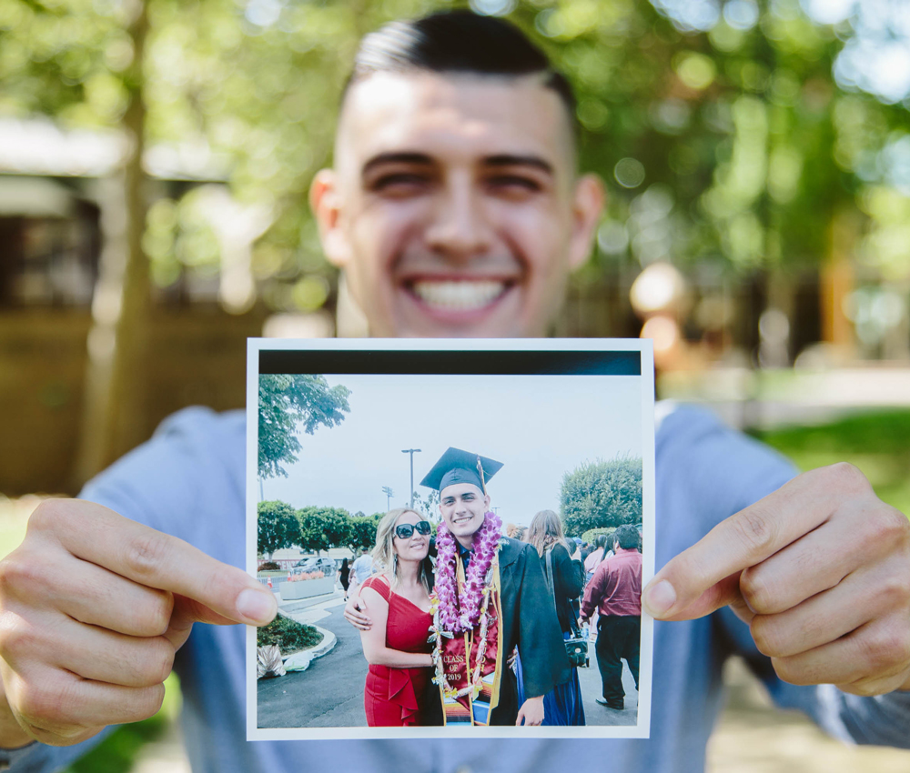 Anthony holds up a photo from his graduation with his mother.