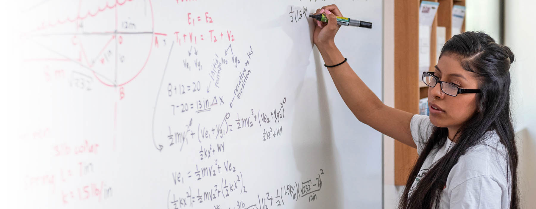 CSU student doing  math on a white board