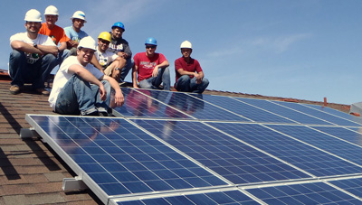 group of young men with hard hats sitting on a roof with solar pannels